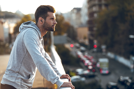 look: In love with his city. Side view of pensive young man in headphones looking away while standing on the bridge Stock Photo