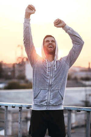 expressing: Everyday winner. Excited young man keeping arms raised and expressing positivity while standing outdoors