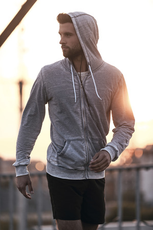 Sporty handsome. Confident young man in sports clothing looking over shoulder while walking outdoors Stock Photo
