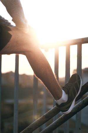 hombre deportista: Preparaci�n de sus m�sculos. Primer plano de hombre que se extiende su pierna antes de ejecutar mientras est� de pie al aire libre