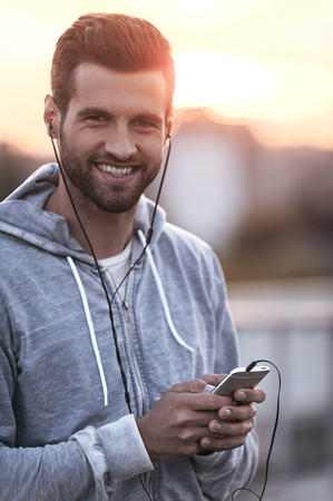 looking to camera: Enjoying music in big city. Smiling young man in headphones holding mobile phone and looking at camera while standing outdoors