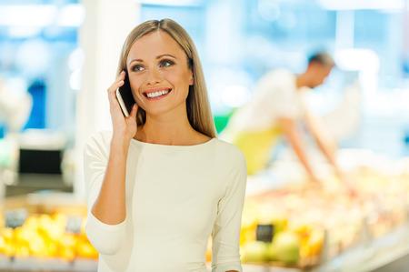 hablando por telefono: Mujer joven feliz hablando por teléfono móvil y sonriendo mientras está de pie en una tienda de alimentos Foto de archivo
