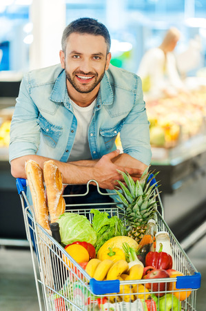 healthy looking: Choosing only healthy food. Cheerful young man leaning at the shopping cart and looking at camera while standing in a food store
