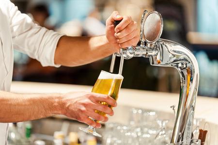 cerveza: Verter la cerveza fresca. Primer plano de joven camarero verter la cerveza, mientras que de pie en la barra del bar