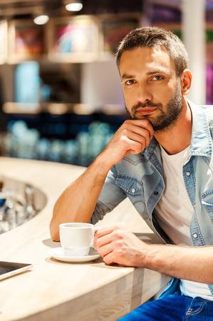 hombres jovenes: Disfrutar de descanso para tomar caf�. Apuesto joven sosteniendo la mano en la barbilla y mirando a la c�mara mientras estaba sentado en la barra del bar