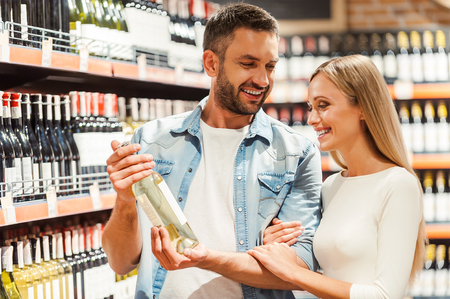 wine store: Joyful young couple choosing wine and smiling while standing in a wine store