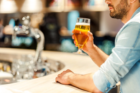 tomando alcohol: Enjoying best beer in town. Cropped image of young man holding glass of beer while sitting at the bar counter