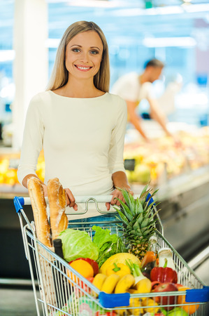 grocery shopping cart: I always make a healthy choice. Beautiful young woman holding hands on shopping cart and smiling while standing in a food store Stock Photo