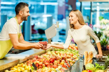 supermarket checkout: Side view of young cashier giving raspberries to female customer while standing in food store Stock Photo