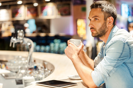 side bar: Coffee for inspiration. Side view of young man holding cup of coffee while sitting at the bar counter Stock Photo