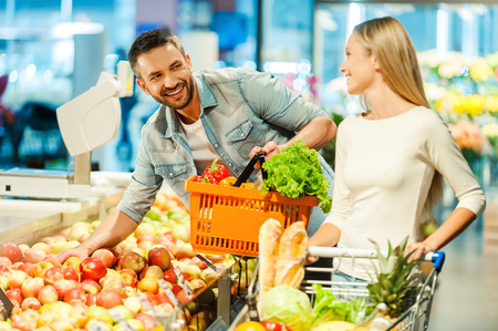 supermarket trolley: Beautiful young couple choosing products in supermarket and looking at each other with smile Stock Photo