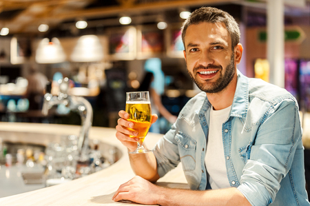 drinks on bar: Beer time. Cheerful young man holding glass of beer and looking at camera while sitting at the bar counter Stock Photo