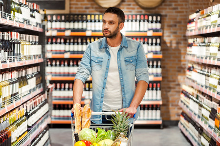 wine store: Choosing the best wine for dinner. Confident young man with shopping cart choosing wine while walking across wine store Stock Photo