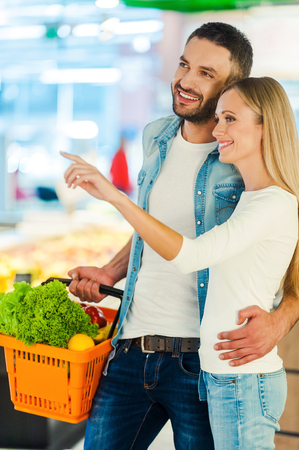 pareja enamorada: Alegre joven pareja sonriendo y apuntando hacia afuera mientras est� de pie en una tienda de alimentos