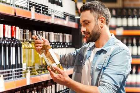 tiendas de comida: Esto debería estar bien. Vista lateral del hombre joven hermoso que sostiene la botella de vino y mirarlo mientras está de pie en una tienda de vinos