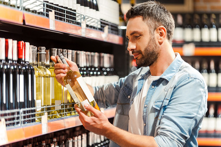 wine store: This should be fine. Side view of handsome young man holding bottle of wine and looking at it while standing in a wine store