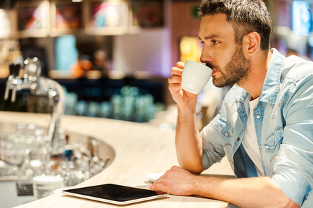 business casual: Coffee break. Side view of young man drinking coffee while sitting at the bar counter Stock Photo