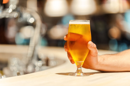 drinks on bar: Fresh beer. Close-up of man holding hand on glass of beer while sitting at the bar counter