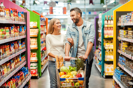 woman shopping cart: Happy young couple bonding to each other and smiling while walking while walking in food store with shopping cart Stock Photo
