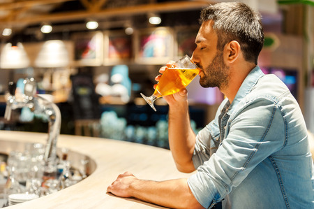 side bar: Enjoying fresh beer. Side view of young man drinking beer and keeping eyes closed while sitting at the bar counter