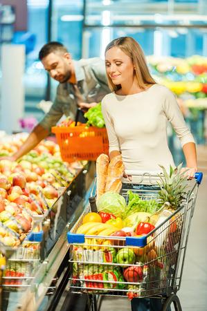 comiendo frutas: Mujer joven sonriente celebración de manzana y mirando a la cámara mientras está de pie en una tienda de alimentos