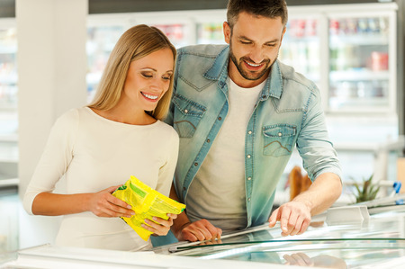 food products: Happy young couple choosing products together while standing near refrigerator in a food store Stock Photo