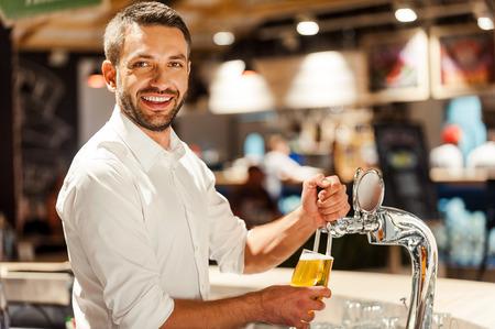 Alleen vers biertje in zijn bar! Gelukkige jonge barman die bier giet terwijl hij achter de balie staat