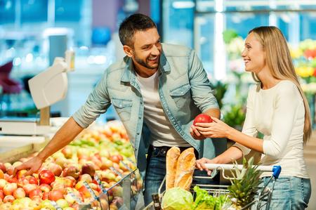 함께 슈퍼마켓에서 사과를 선택하는 아름 다운 젊은 미소 커플