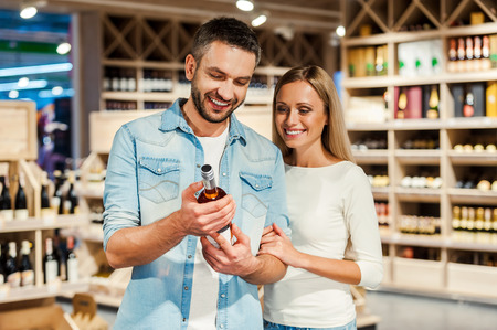 alcohol drinks: Happy young couple choosing wine and smiling while standing in a wine store