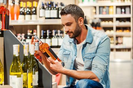 alcool: Beau jeune homme tenant une bouteille de vin en position debout dans un magasin de vins Banque d'images