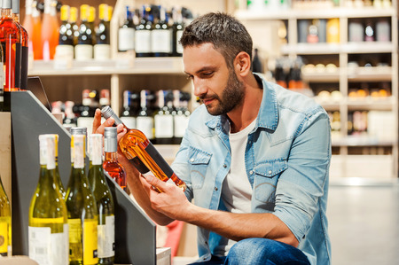 Handsome young man holding bottle of wine while standing in a wine store Stock Photo
