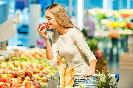 Beautiful young woman holding apple and smelling it with smile while standing in a food store