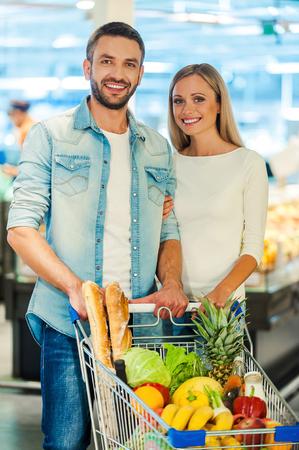 pareja comiendo: Feliz pareja de jóvenes sonriendo y mirando a la cámara mientras está de pie detrás de un carrito de compras en una tienda de alimentos