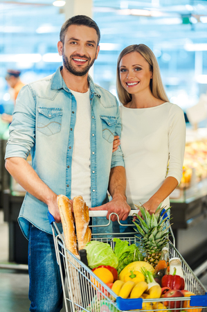 woman shopping cart: Happy young couple smiling and looking at camera while standing behind a shopping cart in a food store Stock Photo