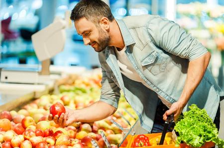 hombre comiendo: Hombre joven hermoso que sostiene la manzana y la bolsa de compras mientras está de pie en una tienda de alimentos