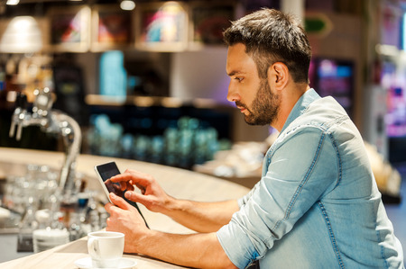 side bar: Side view of young man working on digital tablet while sitting at the bar counter Stock Photo