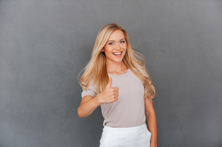 great job: Great job! Joyful young blond hair woman showing her thumb up and looking at camera while standing against grey background Stock Photo