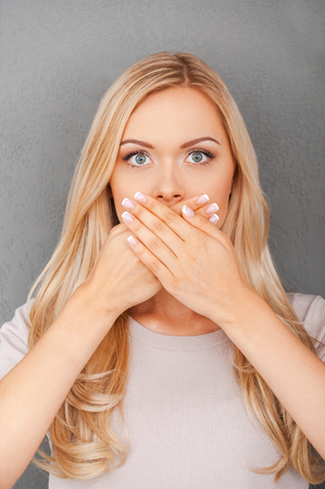 cheveux blonds: Less information. Surprised young blond hair woman covering her mouth and staring at camera while standing against grey background