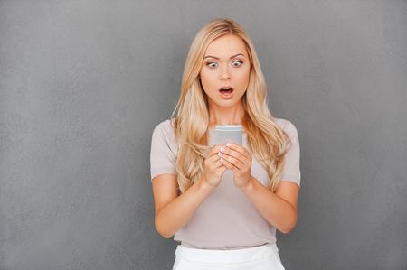 sorpresa: Mensaje impactante. Mujer joven de pelo rubio sorprendido que sostiene el teléfono móvil y mirándolo mientras está de pie contra el fondo gris