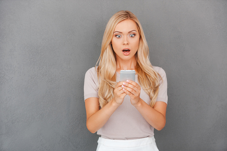 blond hair: Shocking message. Surprised young blond hair woman holding mobile phone and staring at it while standing against grey background Stock Photo