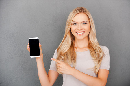 Copy space on her smart phone. Smiling young blond hair woman holding mobile phone and pointing at it while standing against grey background
