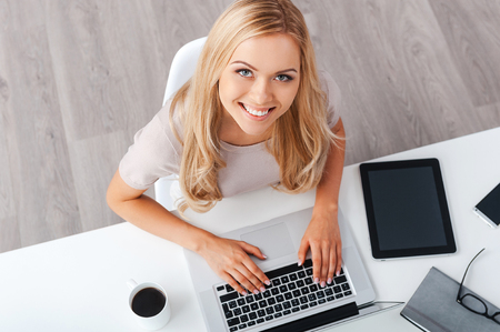 Enjoying productive day. Top view of cheerful young businesswoman working on laptop and looking at camera while sitting at her working place