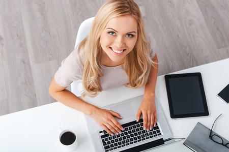 Bénéficiant journée productive. Vue de dessus d'une jeune femme d'affaires gaie travaillant sur ordinateur portable et en regardant la caméra assis à sa place de travail Banque d'images