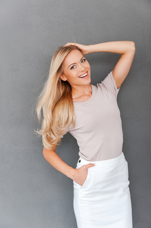 Looking and feeling great! Beautiful young blond hair woman holding hand in hair and looking at camera while standing against grey background
