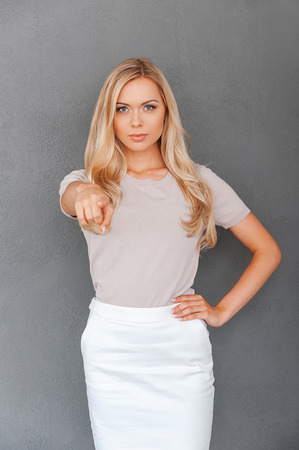 woman pointing: I choose you! Confident young blond hair woman pointing at camera and holding hand on hip while standing against grey background