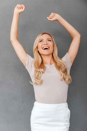 blond hair: Another business victory. Cheerful young blond hair woman keeping arms raised and looking up while standing against grey background