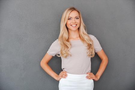 plan éloigné: Confiant en ses capacités. Sourire jeune femme de cheveux blonds se tenant les mains sur les hanches et en regardant la caméra tout en se tenant sur fond gris