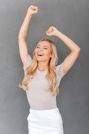 puños cerrados: Celebrando el éxito. Joven mujer emocionada cabello rubio mantener los brazos en alto y mantener los ojos cerrados mientras está de pie contra el fondo gris