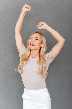 outstretched: Celebrating success. Excited young blond hair woman keeping arms raised and keeping eyes closed while standing against grey background Stock Photo