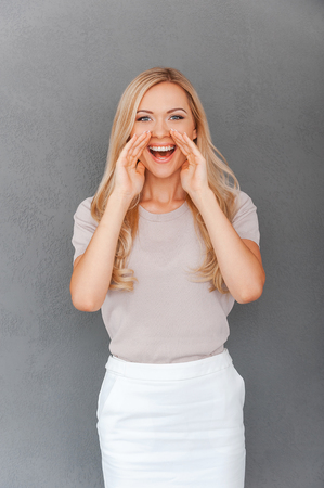 open business: Sharing good news. Happy young blond hair woman holding hands near her mouth and looking at camera while standing against grey background Stock Photo